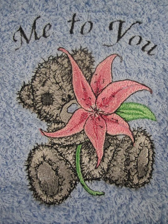 Teddy bear with lily design on embroidered towel