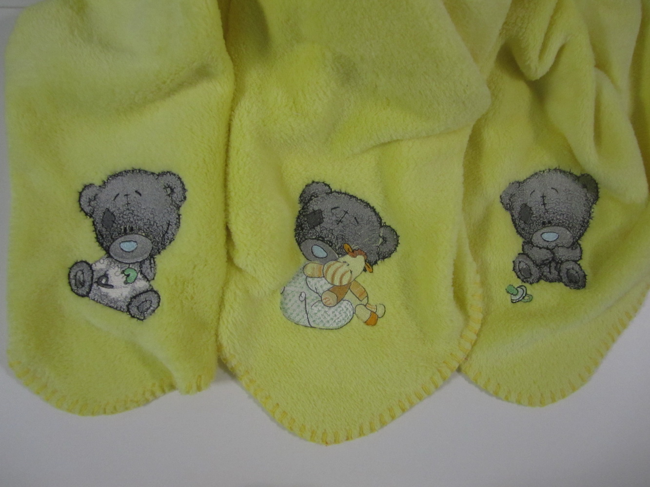 Fleece blanket with cute teddy bears embroidered on it