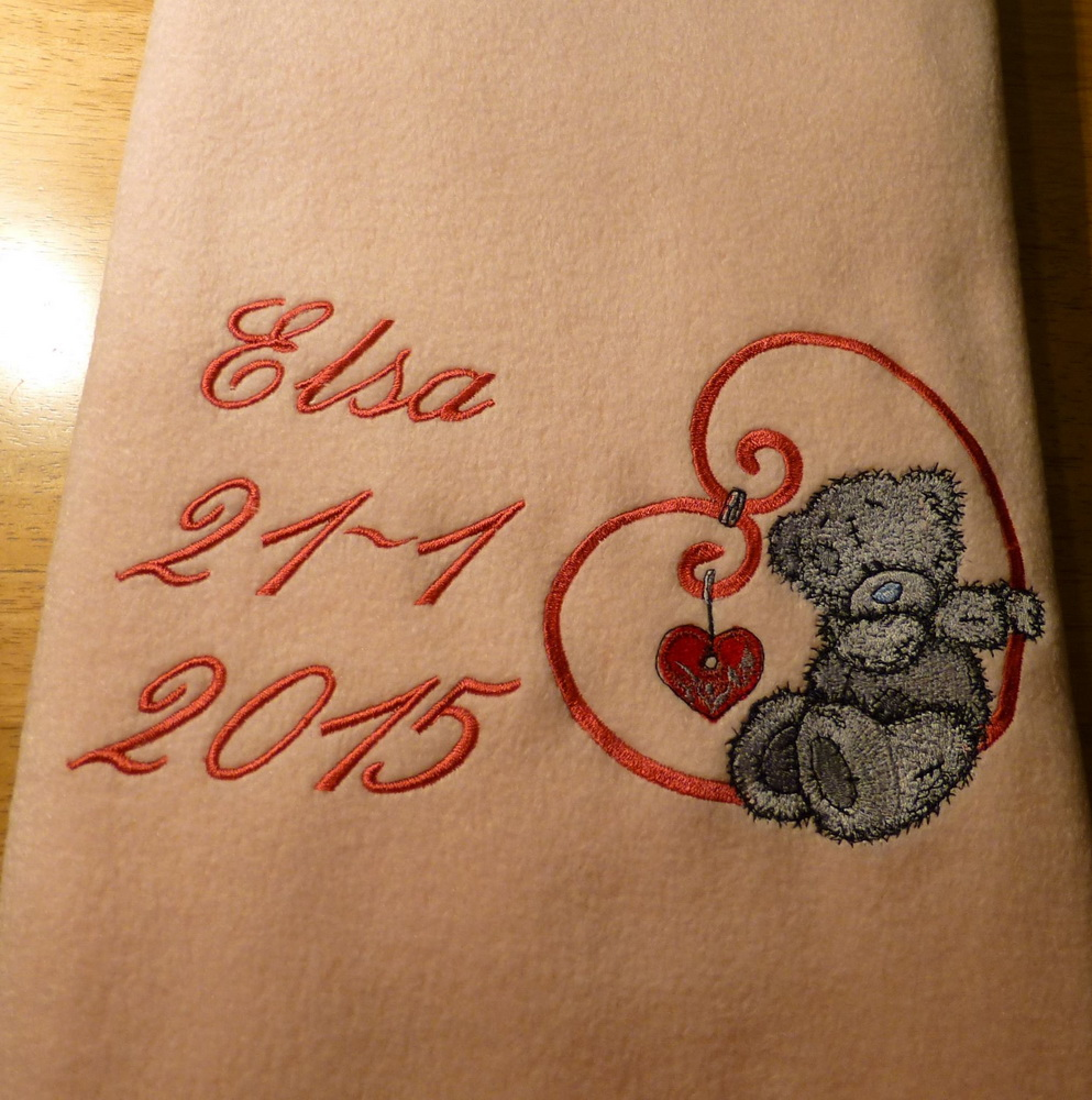 Cute fluffy teddy bear on embroidered blanket