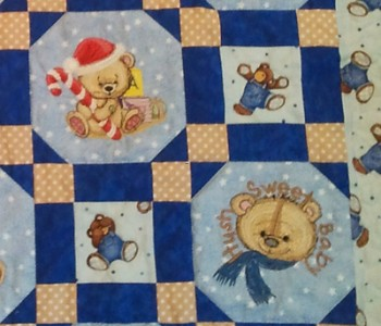 Teddy bears embroidered on blue quilt