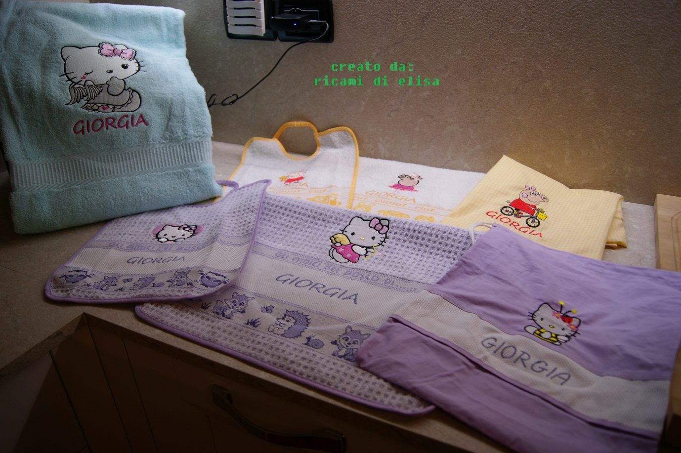 Embroidered Peppa Pig and Hello Kitty designs on towels and bibs