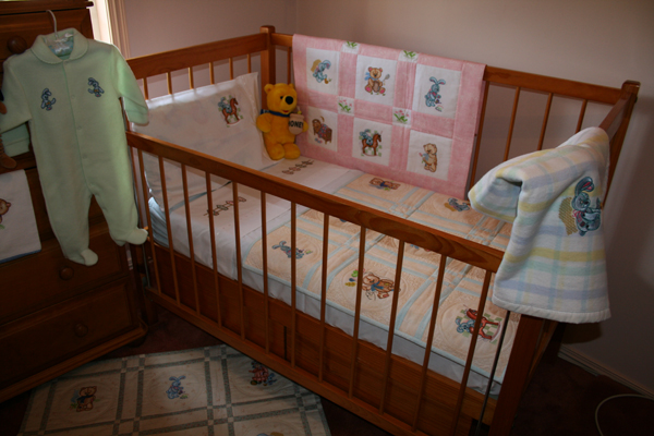 Decorated bed and baby wear with old toys embroidery designs