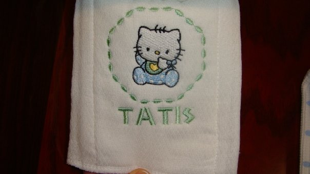 White bath towel with embroidered Hello Kitty baby bib design on it