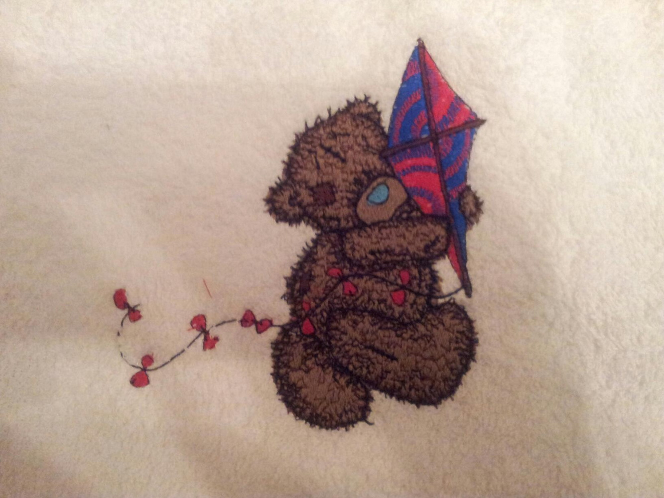 White bath towel embroidered with blue nose teddy bear