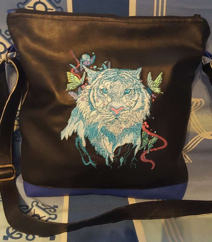Leather bag with embroidered tiger design