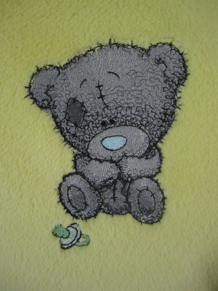 Soft blanket with embroidered teddy bear design on it