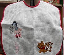 White baby bib embroidered with Winnie Pooh and his best friends