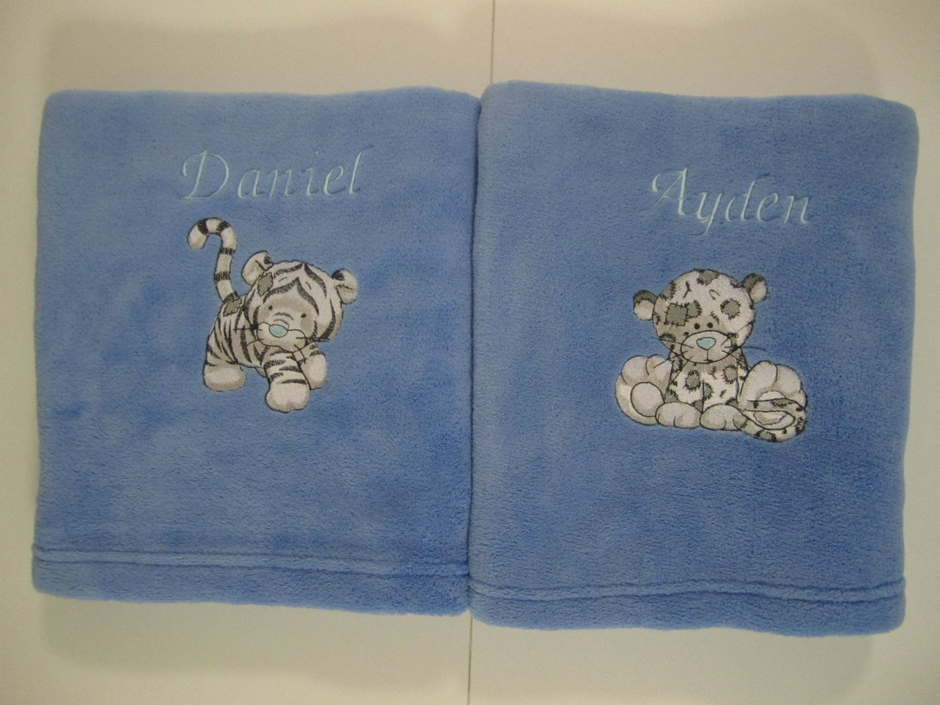 Embroidered Bengal and Leo designs on blanket