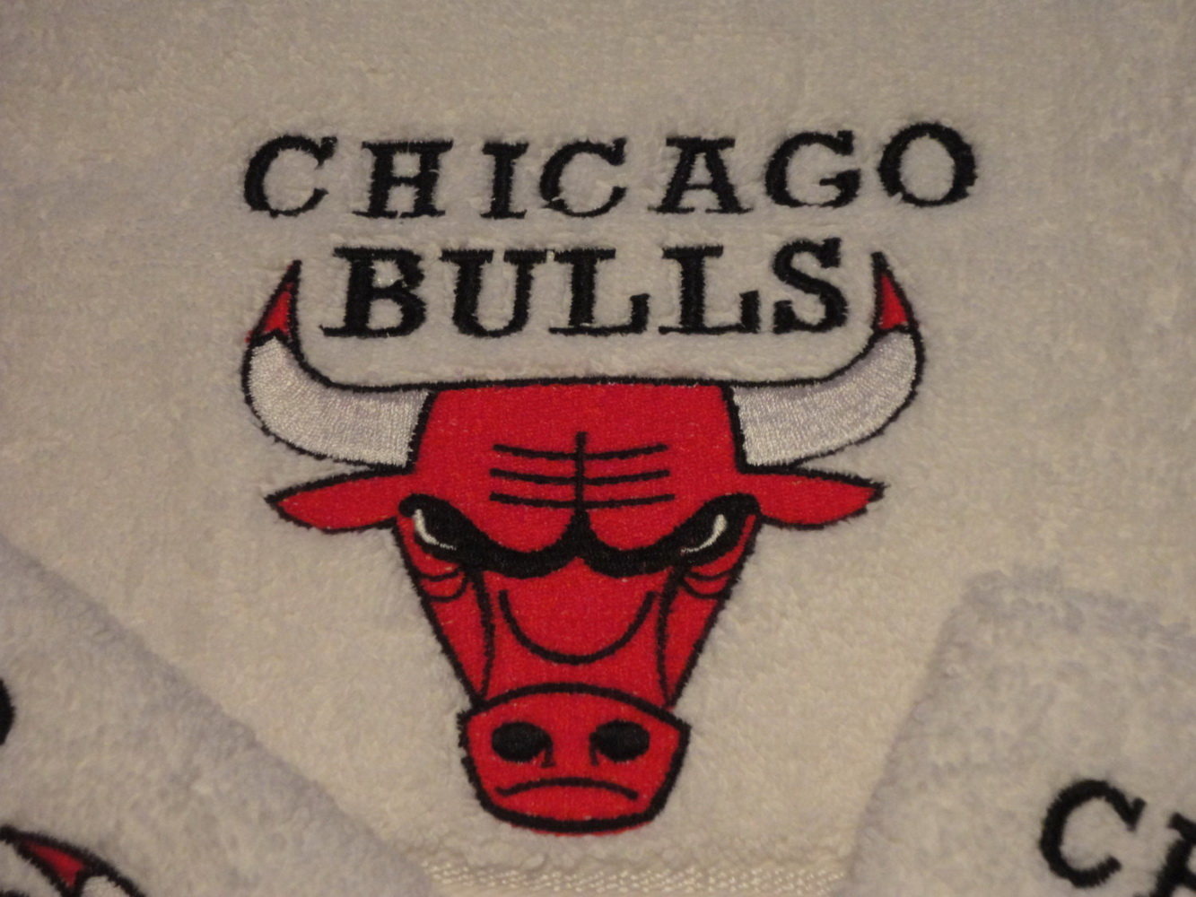 White bath towel with Chicago Bulls embroidered logo on it