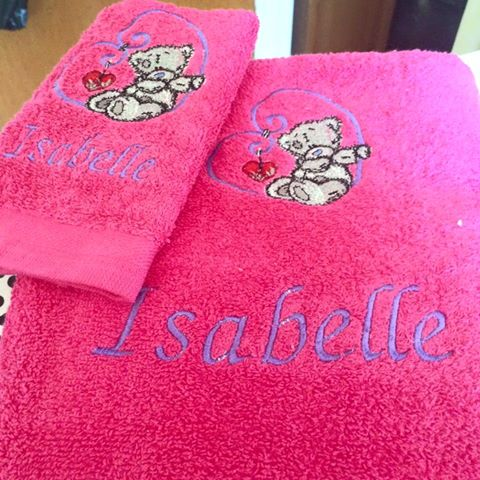 Pink towel with embroidered bear with heart on it