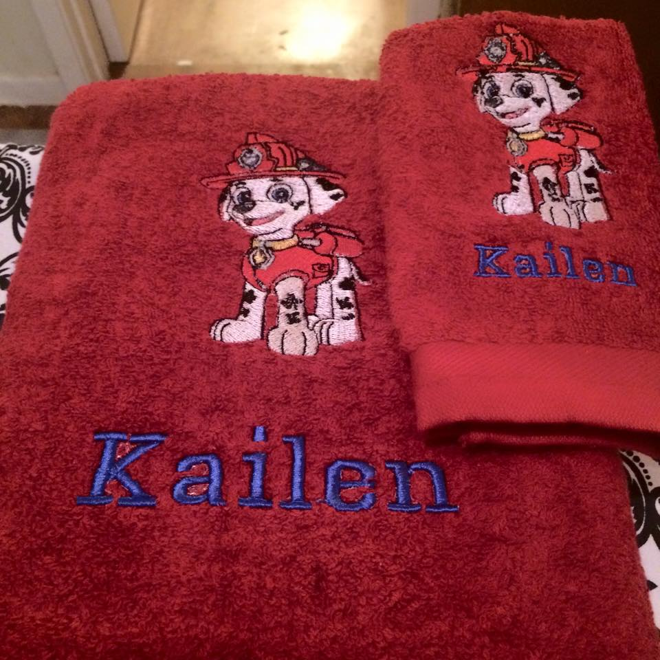 Red embroidered towel with fireman puppy on it