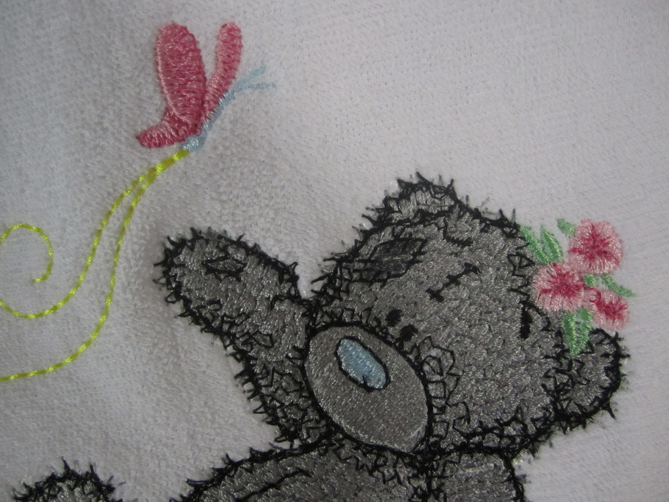 Teddy bear with butterfly embroidered on bib