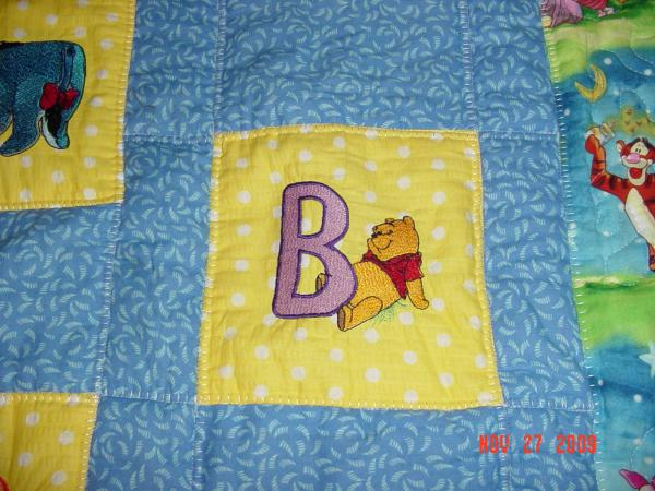 Happy embroidered Winnie pooh letter B design on warm quilt