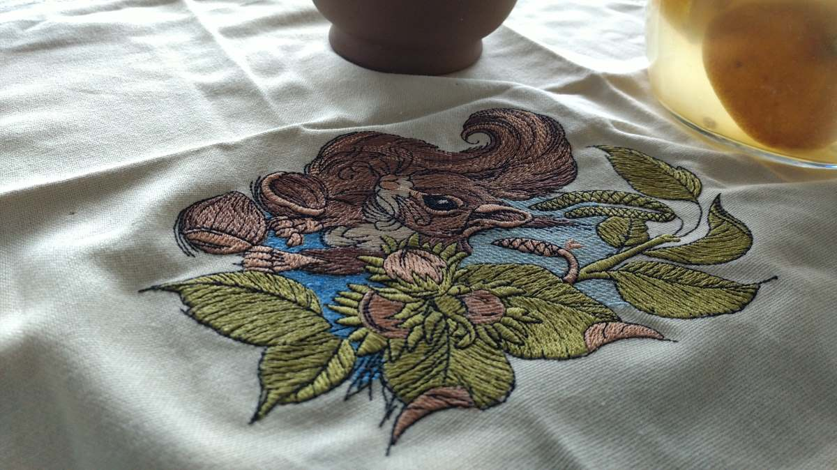 Embroidered napkin with squirrel with hazelnut