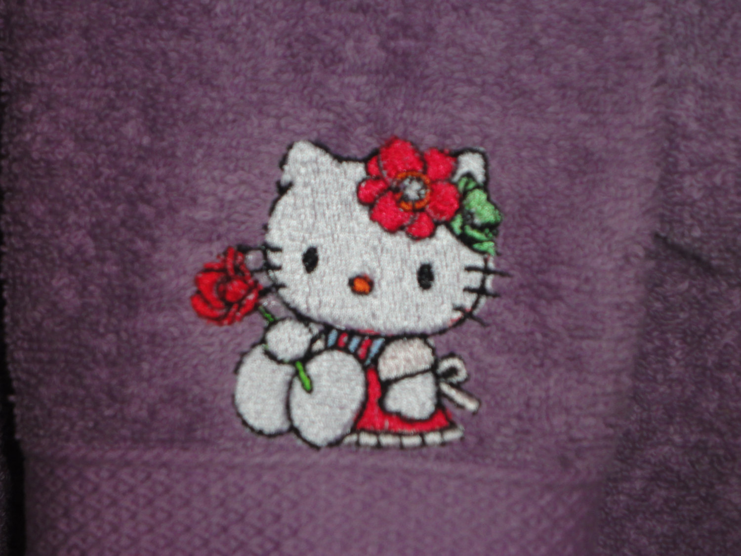 Purple towel with embroidered Hello Kitty on it