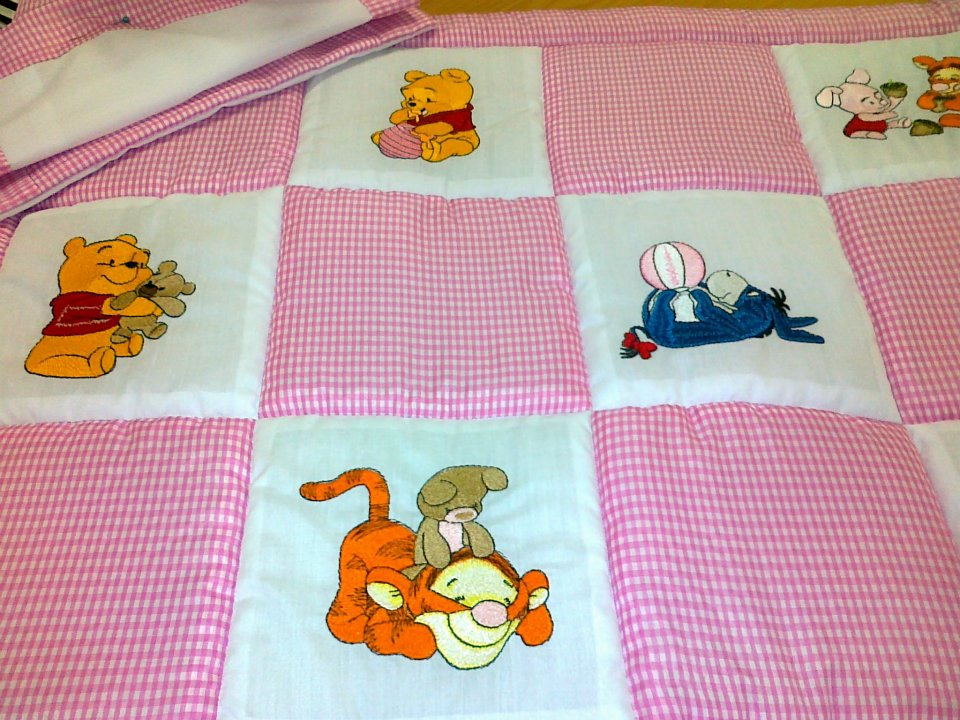 Pink and white embroidered quilt with Pooh designs