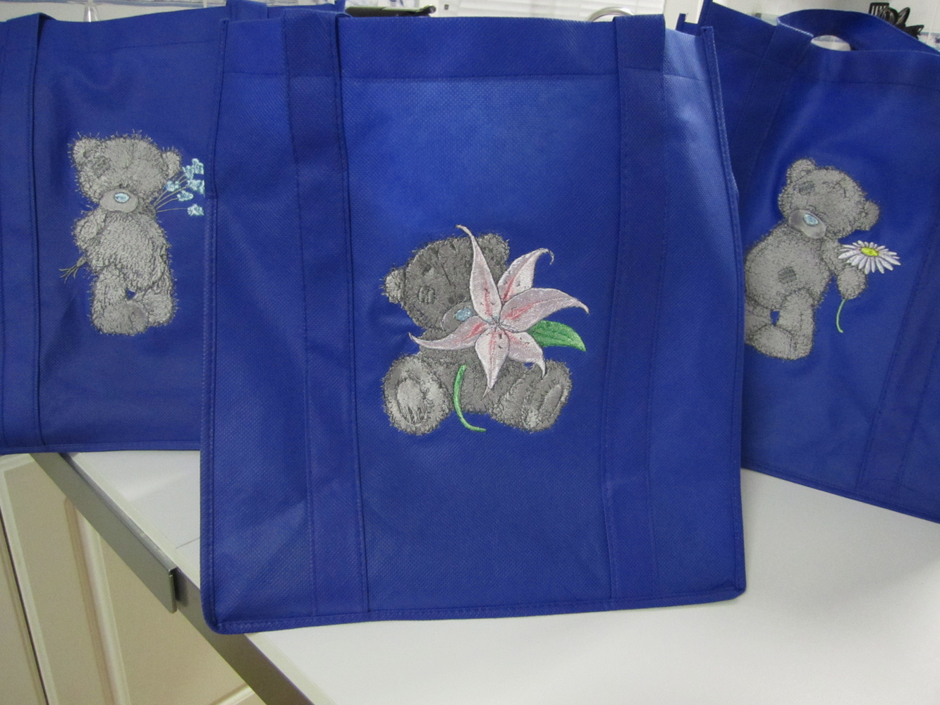 Blue bags embroidered with tatty teddy bears