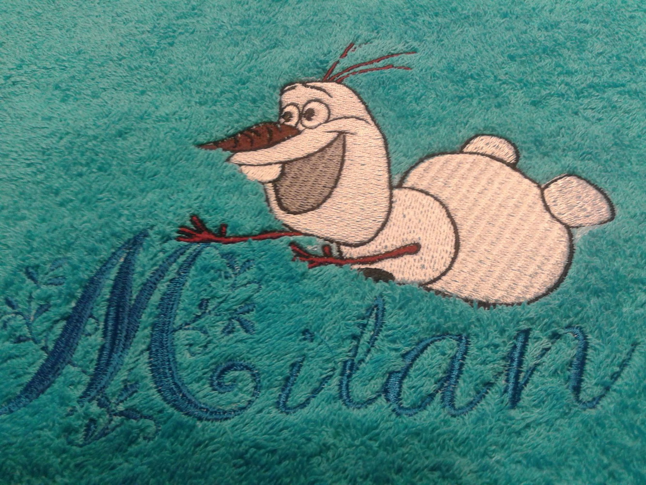 Bath towel with embroidered Olaf on it