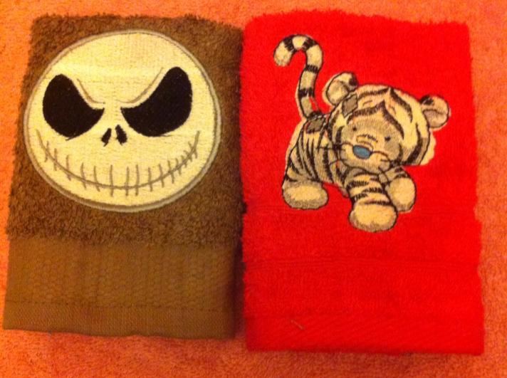 Bath towels with embroidered skull and tiger designs