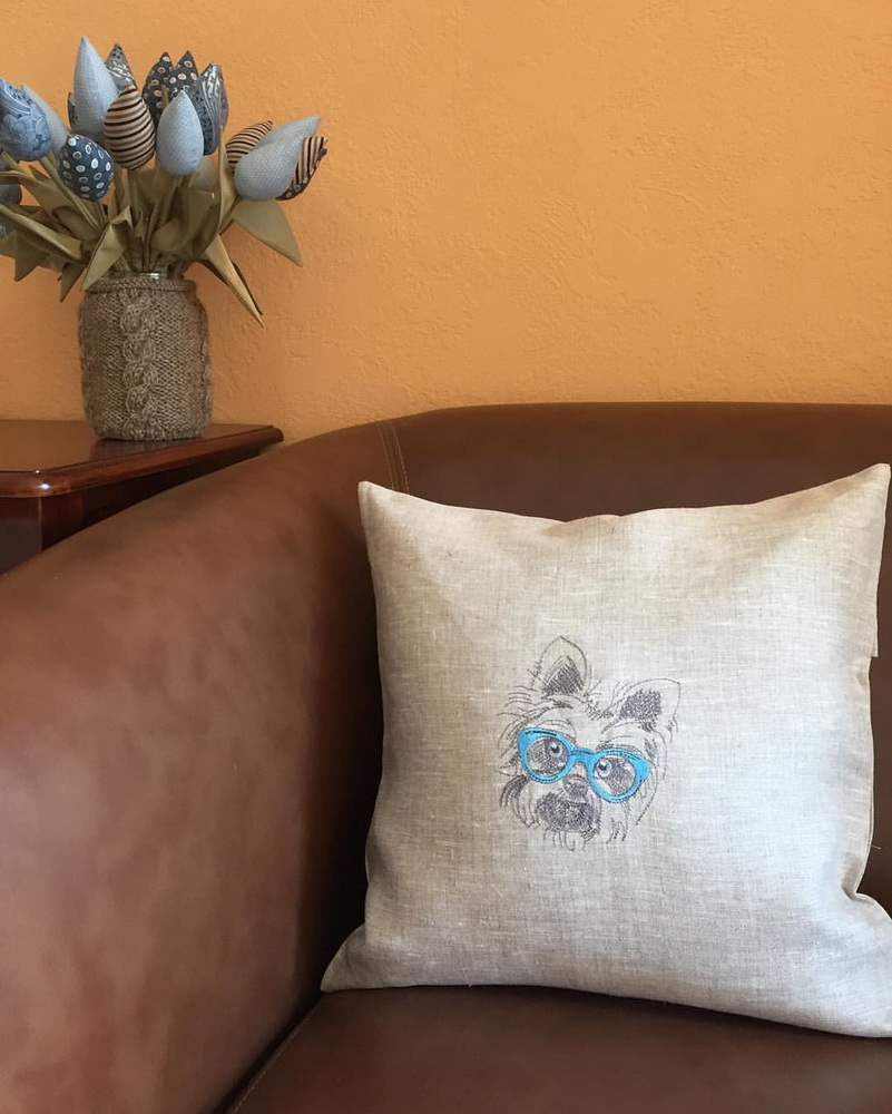 Stylish puppy on embroidered pillowcase