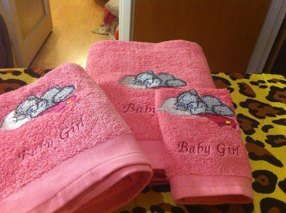 Pink towel with embroidred teddy bear on it
