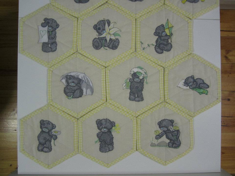 Tatty teddy bear on yellow embroidered quilt