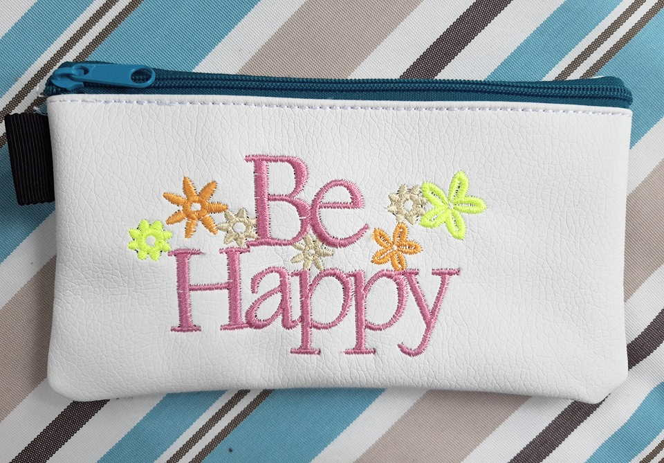 Beauty bag with be happy free embroidery design