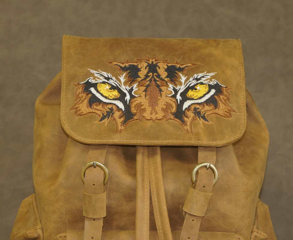 Embroidered leather backpack with tiger eyes design