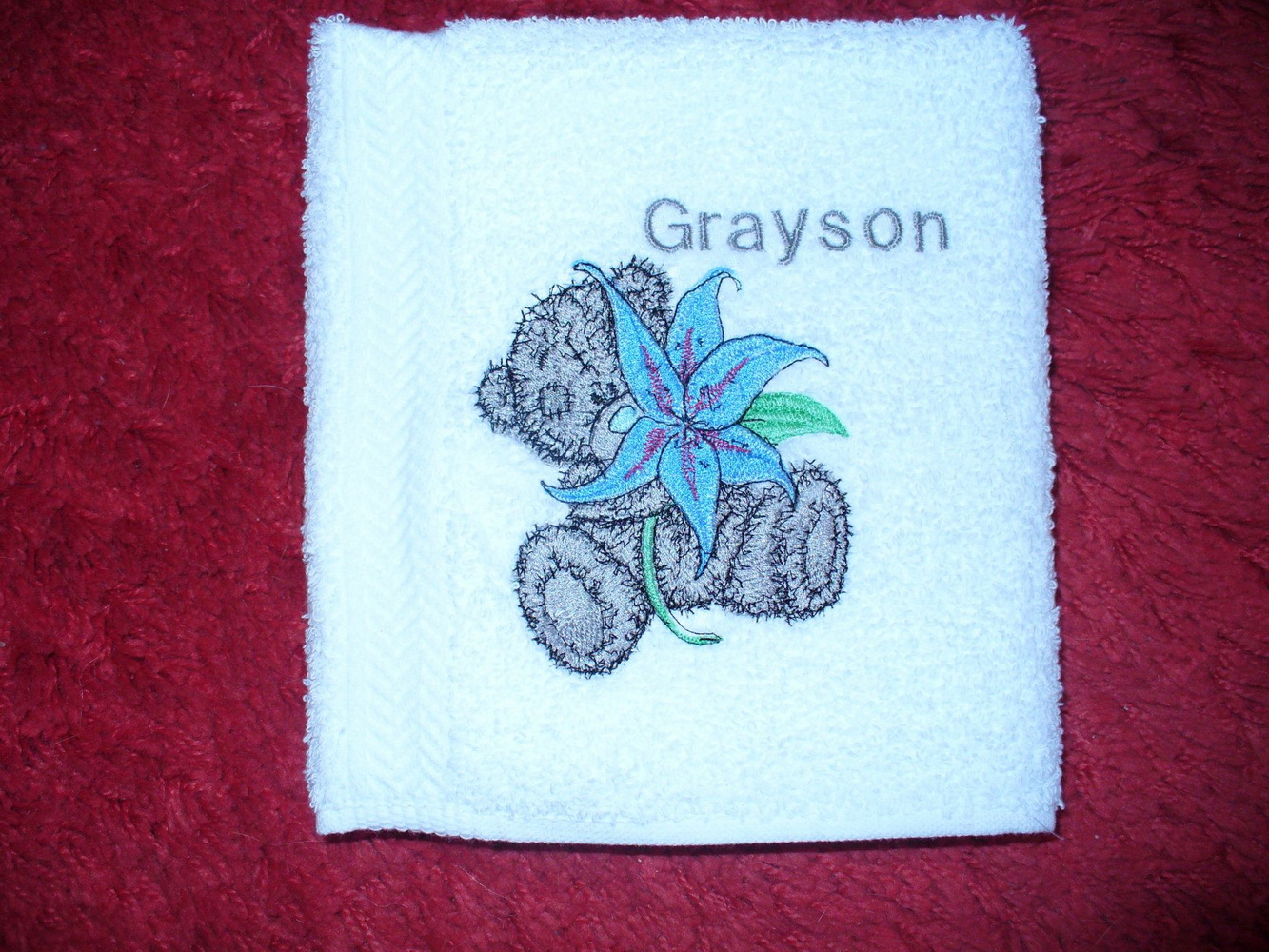 Teddy bear with lily design embroidered on towel