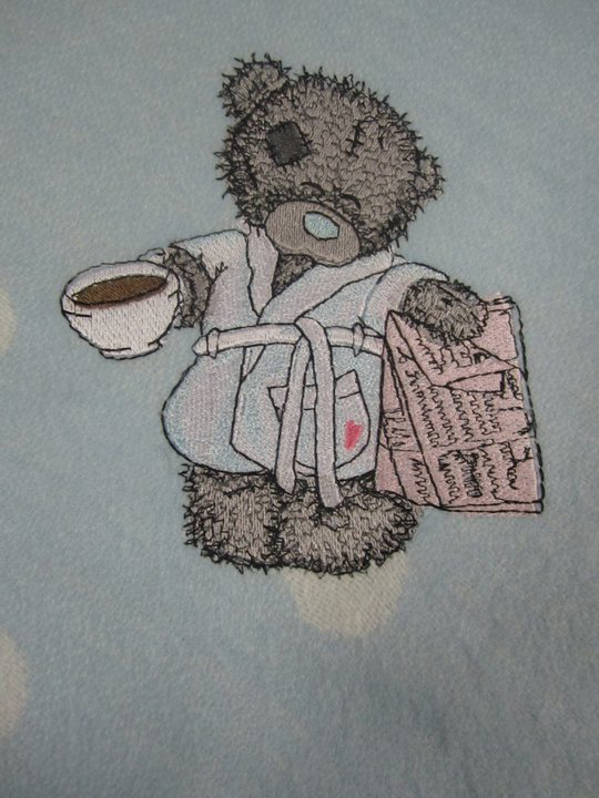 Tatty teddy bear on embroidered polka dot table cloth