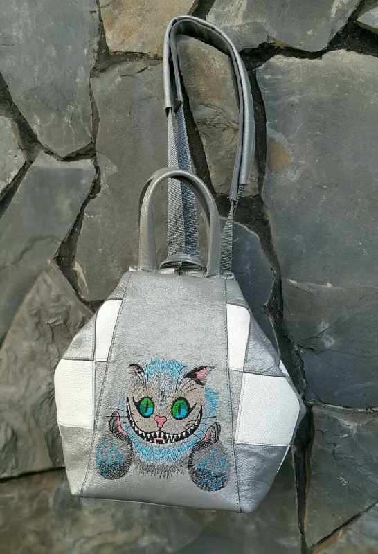 Modern leather backpack with Cheshire cat embroidery