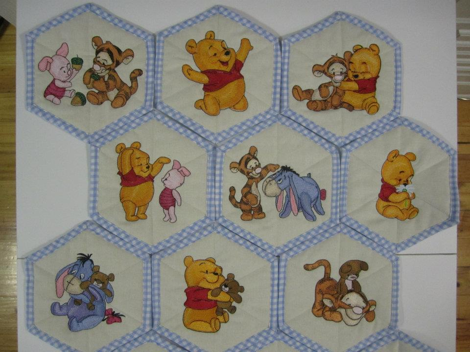 Embroidered Baby Pooh designs on quilt