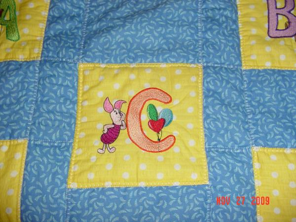 Small embroidered Piglet letter C design on quilt
