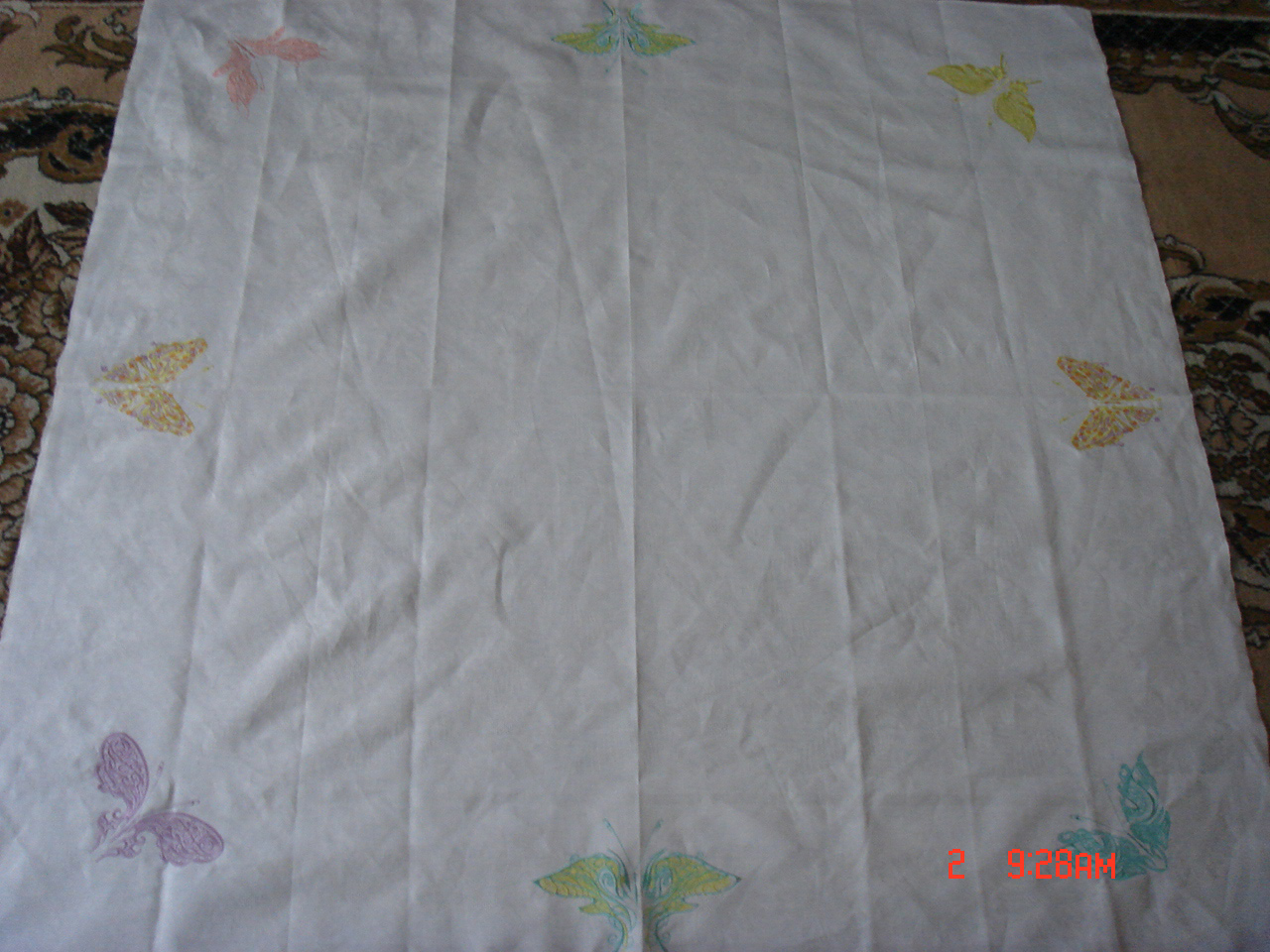 Butterfly designs on embroidered white table cloth
