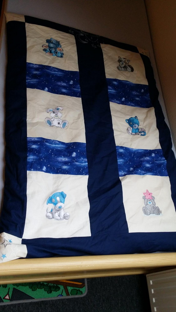 Baby quilt with cute blue nose friends embroidered on it
