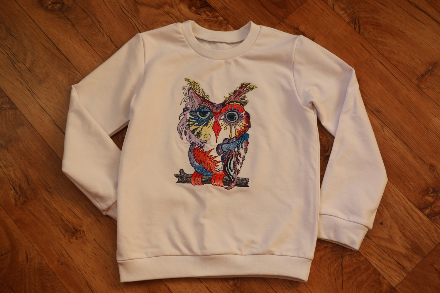 White kid's hoodie with embroidered colorful owl