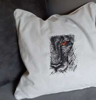 Embroidered pillow with lion eyes design
